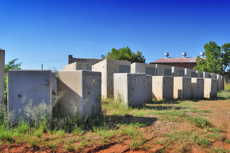 Unsafe Safe. A grouping of abandoned heavy duty safes in a yard with grass growing all round the base. Concrete and steel construction. An unsafe investment or royalty free stock photo