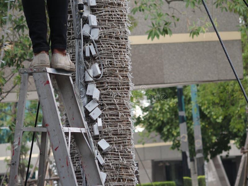 Unsafe step on ladder. Man working on unsafe last step on ladder stock image