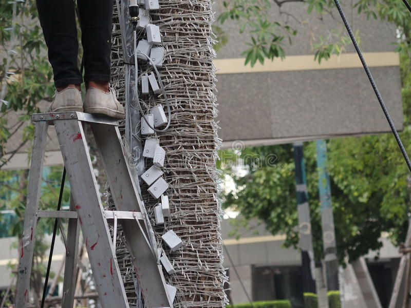 Unsafe step on ladder. Man working on unsafe step on ladder remove led light royalty free stock photography