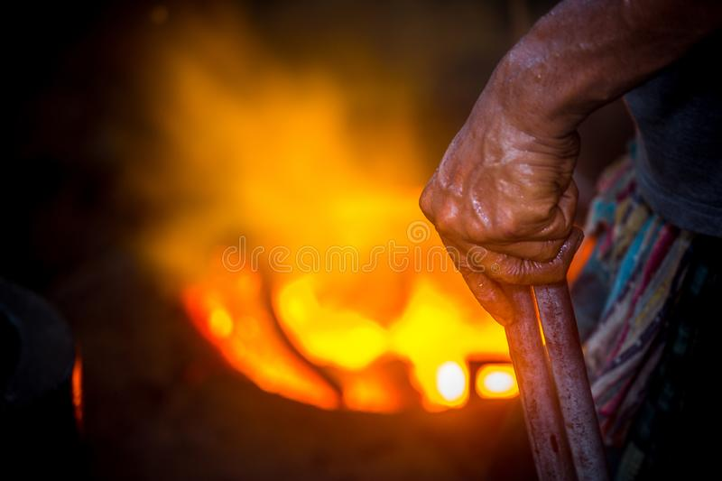 Unsafe worker hands. A local steel machine parts making yard worker melting scrap on hot furnace.  stock photo