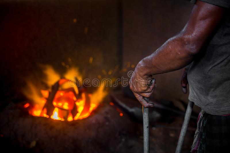 Unsafe worker hands. A local steel machine parts making yard worker melting scrap on hot furnace.  royalty free stock photo