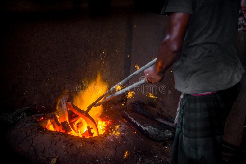 Unsafe worker hands. A local steel machine parts making yard worker melting scrap on hot furnace.  stock images