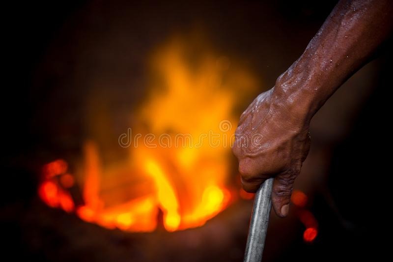 Unsafe worker hands. A local steel machine parts making yard worker melting scrap on hot furnace.  royalty free stock photos