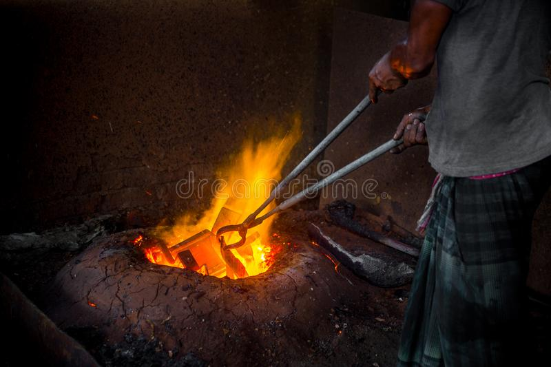Unsafe worker hands. A local steel machine parts making yard worker melting scrap on hot furnace.  stock image