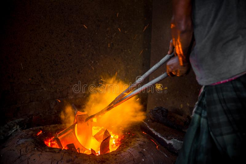 Unsafe worker hands. A local steel machine parts making yard worker melting scrap on hot furnace.  royalty free stock image