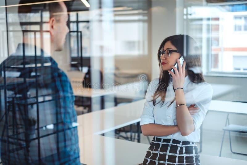 Unsatisfied affärskvinna som talar på telefonen medan kollega I arkivfoton