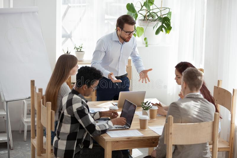 Unsatisfied boss company with employees at boardroom stock photo