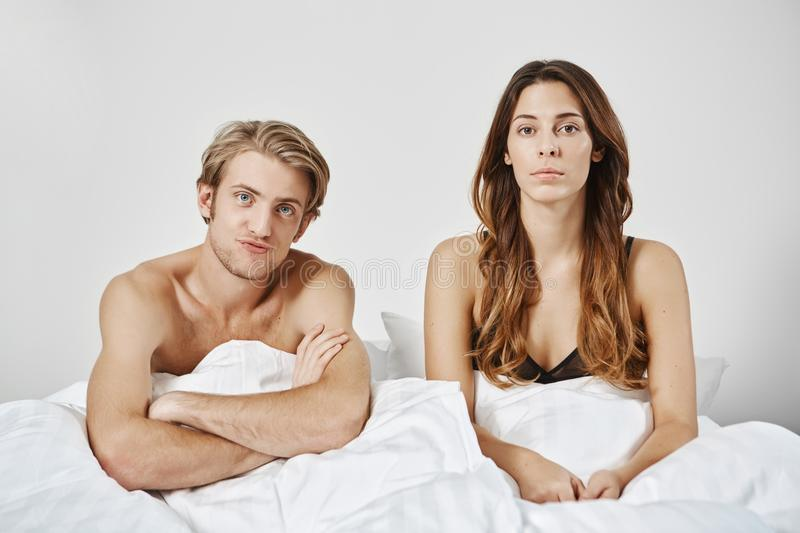 Unsatisfied disappointed couple sitting in bed under blanket, looking at camera, boyfriend crosses hands in confusion stock photography