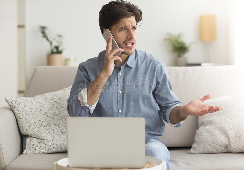 Unsatisfied Guy Complaining About Problems With Laptop By Phone Indoor. Hotline And Bad Service. Man Complaining About Problems With Laptop By Mobile Phone stock images
