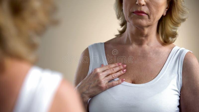 Unsatisfied hög dam som ser hennes hals i spegeln, anti--ålder kosmetisk omsorg arkivfoto