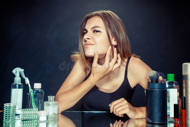 Unsatisfied jonge vrouw die zelf haar bekijken in spiegel op zwarte achtergrond stock afbeeldingen