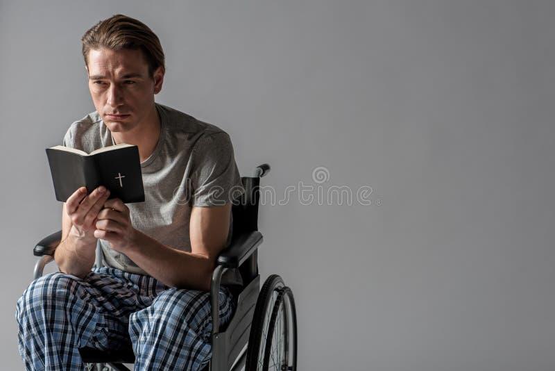 Unsatisfied manlig person med den läs- bibeln för handikapp arkivbilder