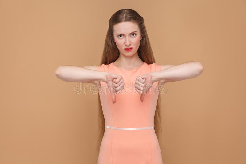 Unsatisfied vrouw toont duimen die beneden en camera bekijken stock foto's