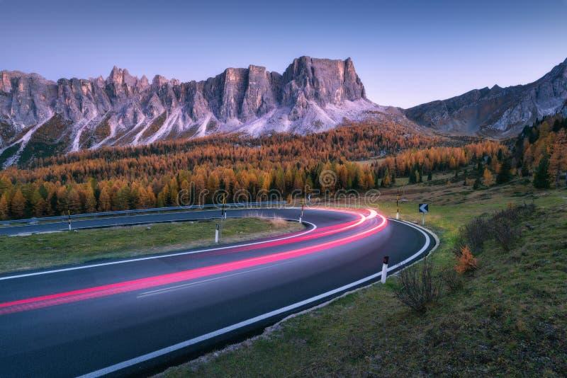 Unscharfe Autoscheinwerfer auf kurvenreicher Straße in den Bergen an der Dämmerung lizenzfreie stockbilder