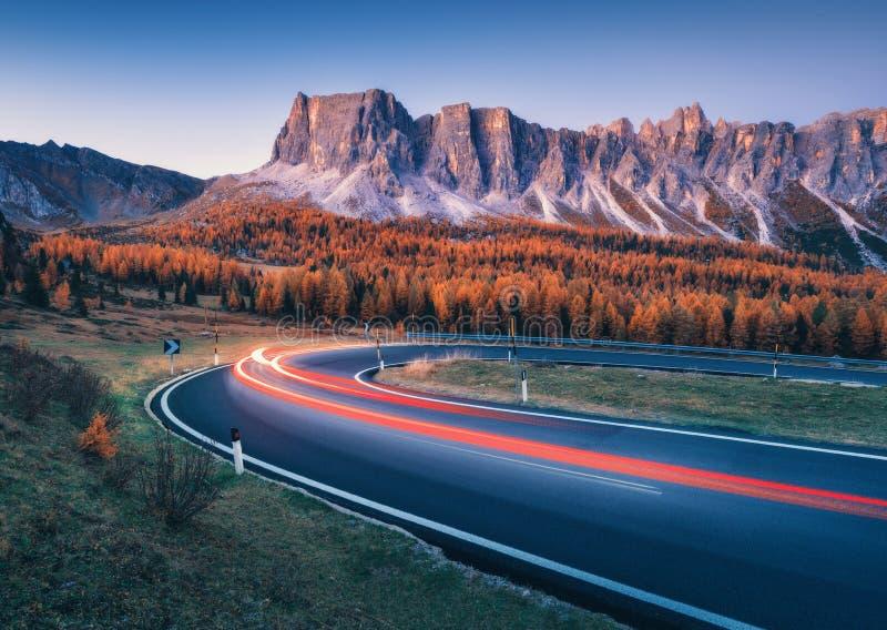 Unscharfe Autoscheinwerfer auf kurvenreicher Straße in den Bergen an der Dämmerung stockbild
