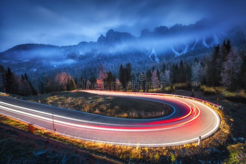 Unscharfe Autoscheinwerfer auf kurvenreicher Straße in den Bergen nachts lizenzfreie stockfotos