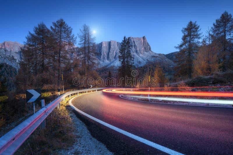 Unscharfe Autoscheinwerfer auf kurvenreicher Straße in den Bergen nachts stockbilder
