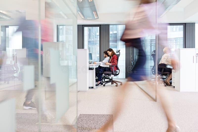 Unscharfe Bewegung der Geschäftsfrau gehend mit den Kollegen, die im Hintergrund im Büro arbeiten stockbild