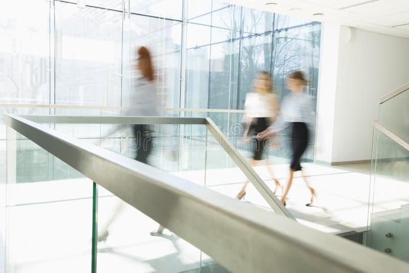 Unscharfe Bewegung von den Geschäftsfrauen, die am Büroflur gehen stockbilder