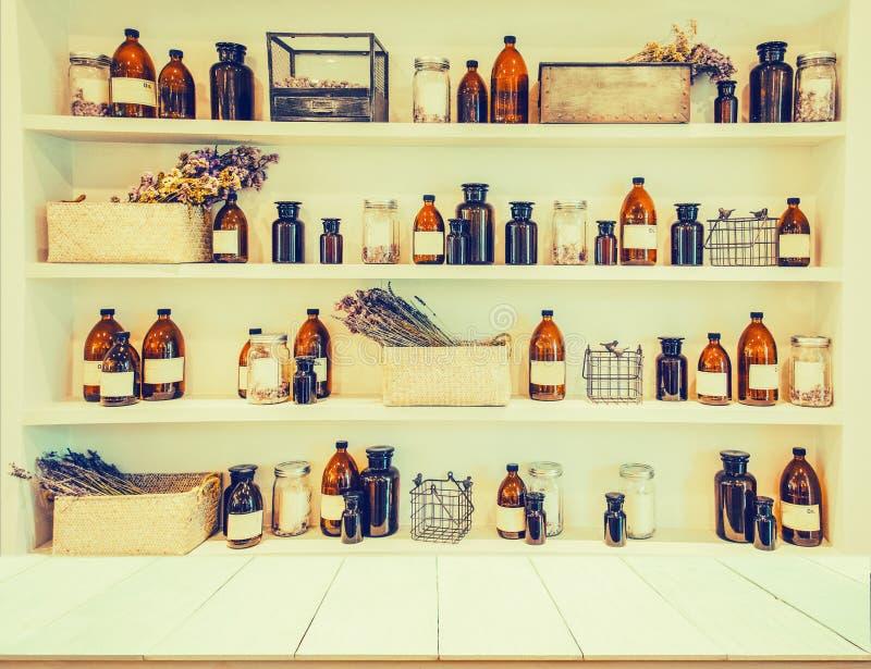 Unscharfe Bild-Badekurortcollagen-Reihe, hölzerne Tabellenregal Flasche mas lizenzfreie stockfotos