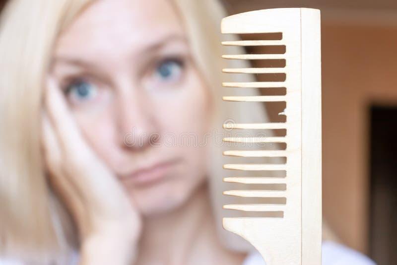 Unscharfe blonde Frau mit einem defekten Kamm in ihrer Hand lizenzfreie stockfotografie