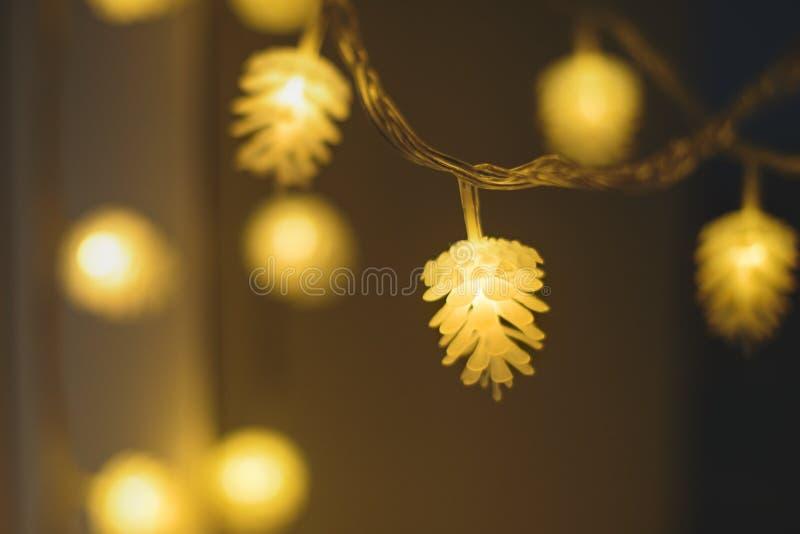Unscharfe gelbe Weihnachtslichter in Form von Kegeln auf dunklem Hintergrund, niedrige Schärfentiefe stockfotos