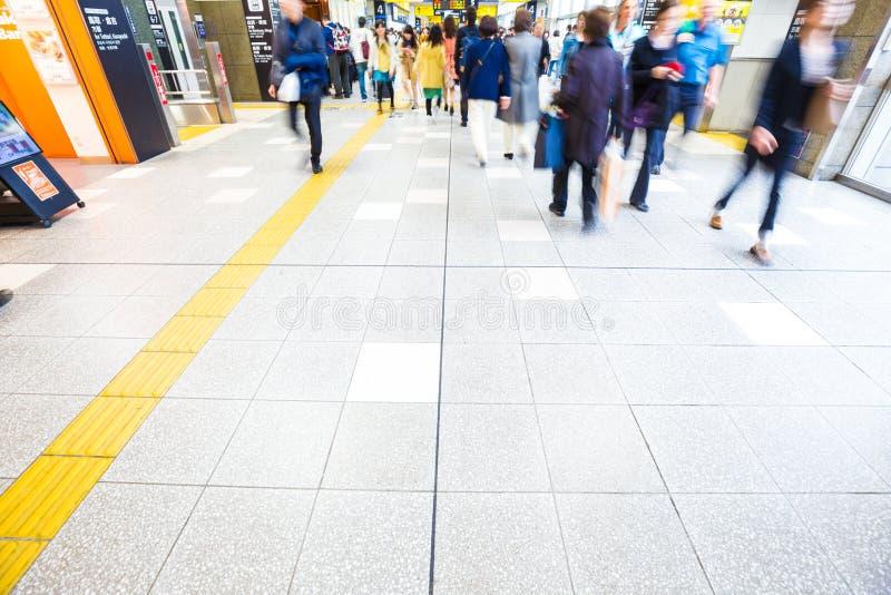Unscharfe Geschäftsleute, die für Reise in der Bahnstations-Reise hetzen stockfotografie