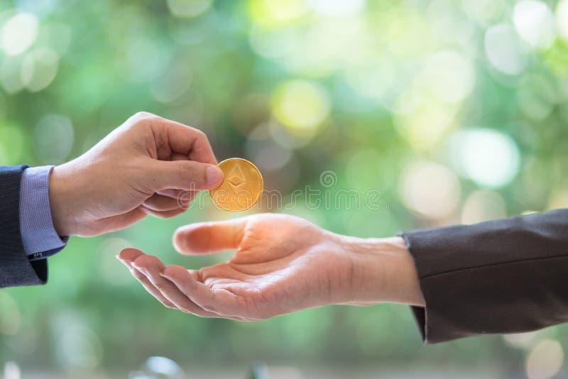 Unscharfe Hände von zwei Geschäftsmännern handeln Münze von ethereum Symbolische Münzen von ethereum elektronischer Geldwechsel, stockfoto