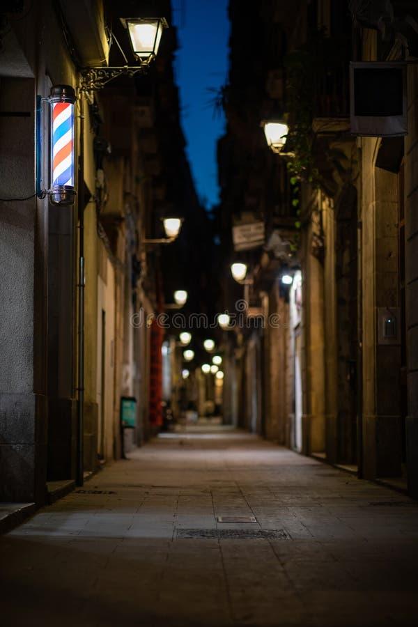 Unscharfe im Stadtzentrum gelegene Gasse nachts mit Friseursalon oder hairdresser& x27; s-Zeichen auf der Wand stockbilder