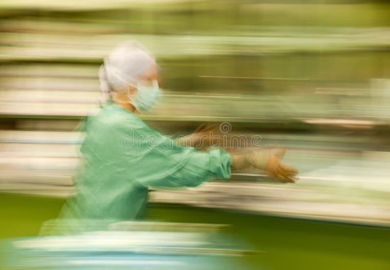 Unscharfe Krankenschwester, die besetzte Funktion laufen lässt lizenzfreie stockfotografie