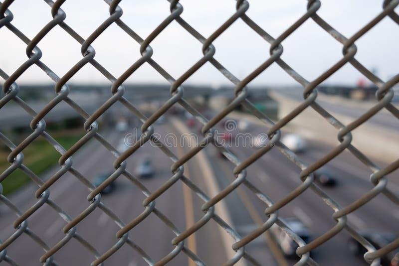 Unscharfe Landstraßenansicht durch einen metallischen Zaun stockbilder