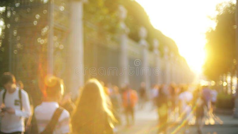 Unscharfe Leute gehen bei schönem Sonnenuntergang lizenzfreie stockfotos