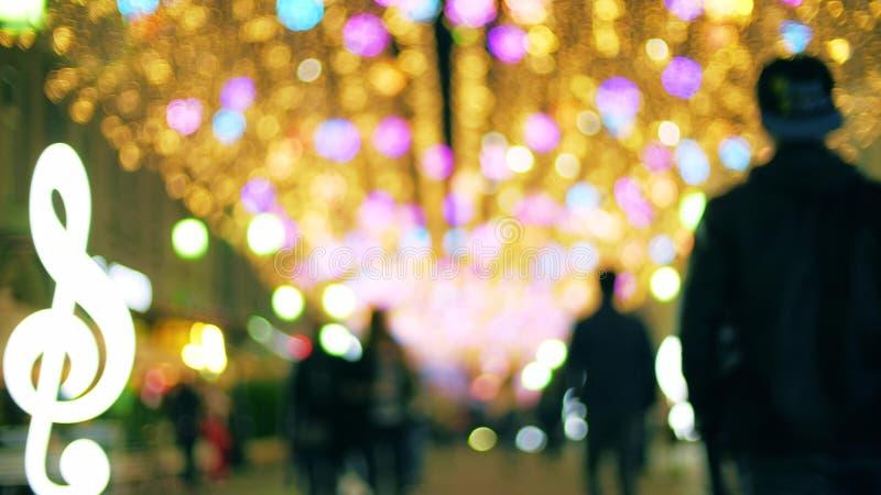 Unscharfe Leute gehen entlang belichtete Fu?g?ngerzone am Abend lizenzfreies stockbild