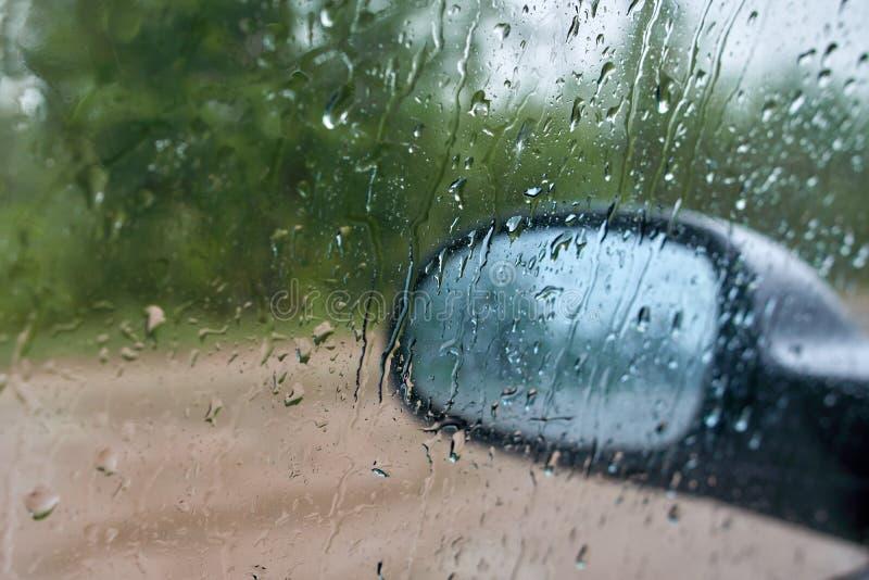 Unscharfe Regentropfen auf dem Seitenfenster des Autos Hinter dem Glas können Sie den Seitenspiegel mit blured Reflexionen sehen lizenzfreie stockfotografie