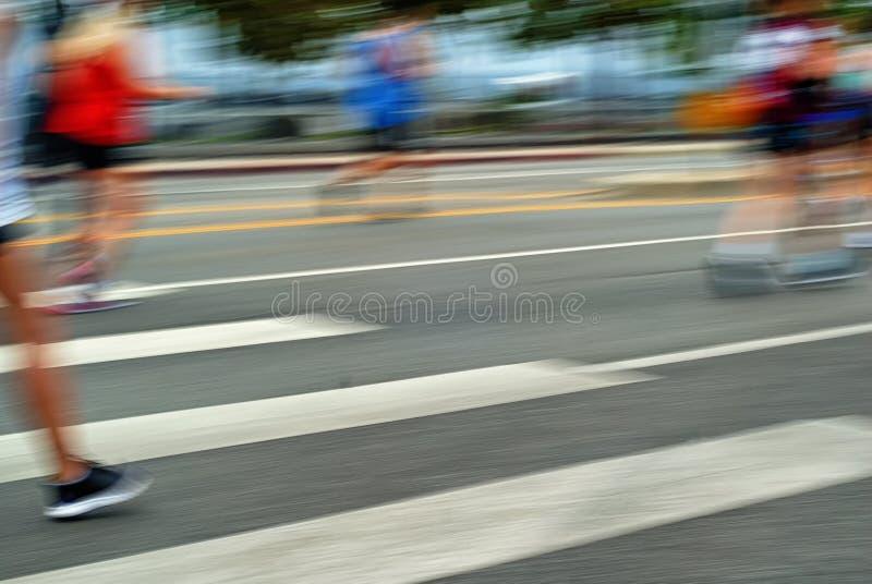 Unscharfe Rennläufer laufen über einen Querweg in der Fahrbahn stockfoto