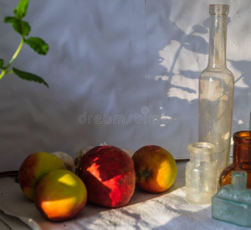 Unscharfe rote gelbe ?pfel, roter Granatapfel, tadelloses Blatt und Weinleseflaschen im Sonnenlicht mit Schatten Abschluss oben stockfotografie