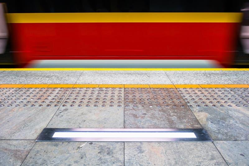 Unscharfe rote Untergrundbahn in Warschau Polen, Tastpflasterung für VI stockbild