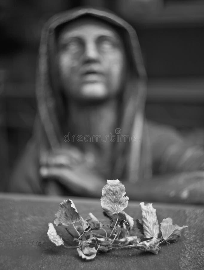 Unscharfe Skulptur einer Sorgen machenden Frau über einem Grab herein mit einem trockenen stockbilder
