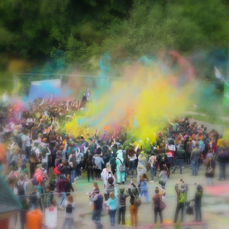 Unscharfe unerkennbare glückliche junge Leute feiern Holi-Festival Bunte Pulverexplosion, selektiver Fokus lizenzfreies stockbild