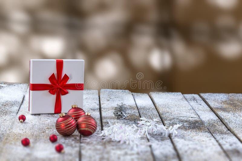 Unscharfer bokeh roter Flitter heller Hintergrund Cristmas-Szene, Geschenksatz roter ribon Holztisch stockfotografie