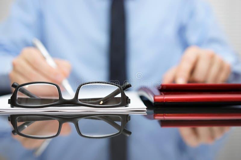 Unscharfer Geschäftsmann arbeitet im Büro, Fokus ist auf eyeglasse stockfoto