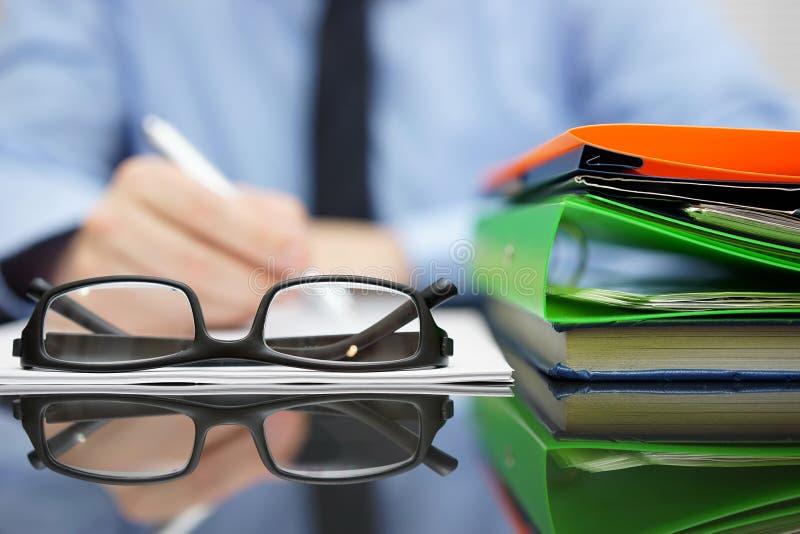 Unscharfer Geschäftsmann schreibt Dokument, Fokus auf Gläsern und FO lizenzfreie stockfotos