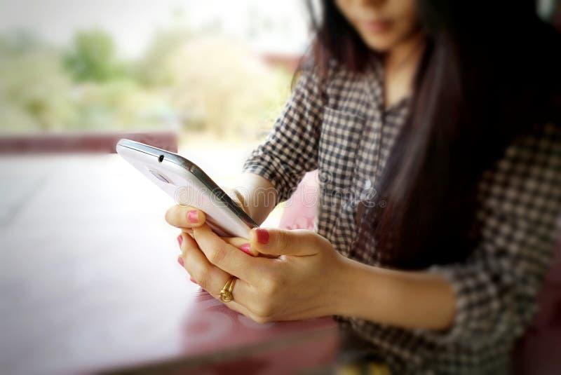 Unscharfer Hintergrund der Hand des jungen Mädchens, die Mobiltelefon hält stockbild