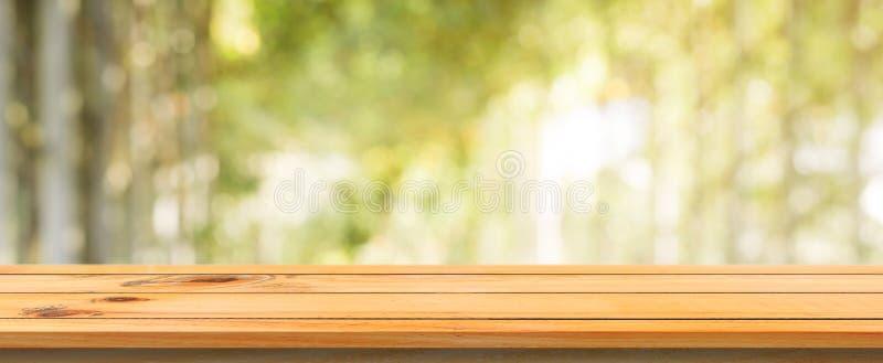 Unscharfer Hintergrund des hölzernen Brettes leere Tabelle Braune hölzerne Tabelle der Perspektive über Unschärfebaum-Waldhinterg