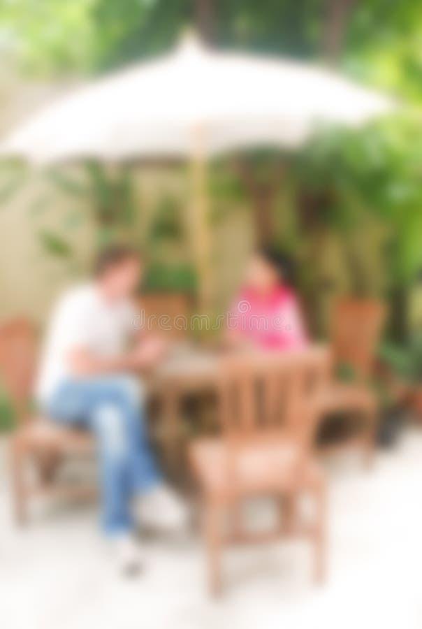 Unscharfer Hintergrund, Mann und Frau sprechen oder Diskussion etwas, Unschärfebildkonzept lizenzfreie stockbilder