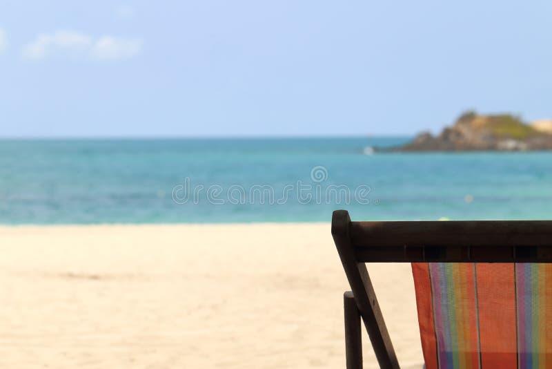 Unscharfer Meerblick für Hintergrund mit Teil buntem deckchair als Vordergrund lizenzfreies stockbild