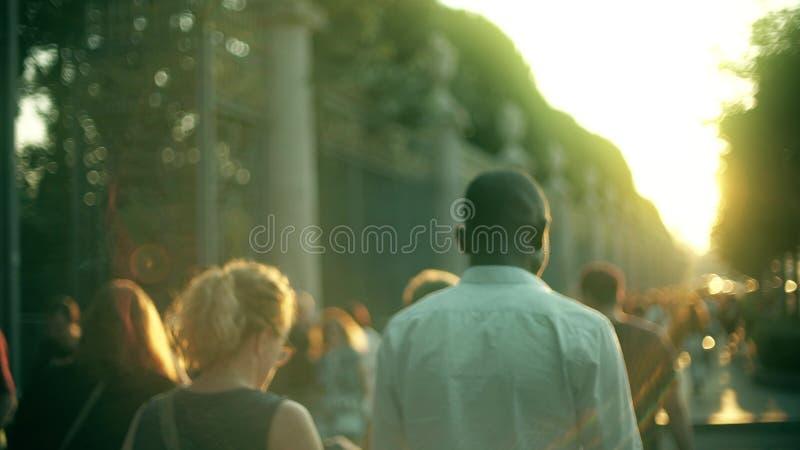 Unscharfer nicht identifizierter Leuteweg bei Sommersonnenuntergang stockbilder