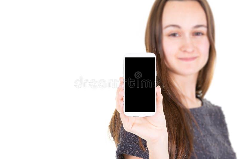 Unscharfer schöner attraktiver hübscher youn Mädchen-Holding Smartphone mit leerem schwarzem Schirm lizenzfreie stockfotografie