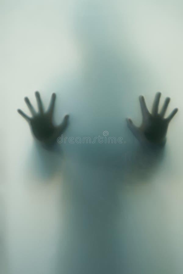 Unscharfer Schatten einer Grausigkeitsfrau Die Hände auf dem Glas Gefährliche Person hinter Mattglas Person des Geheimnisses Ha lizenzfreies stockbild