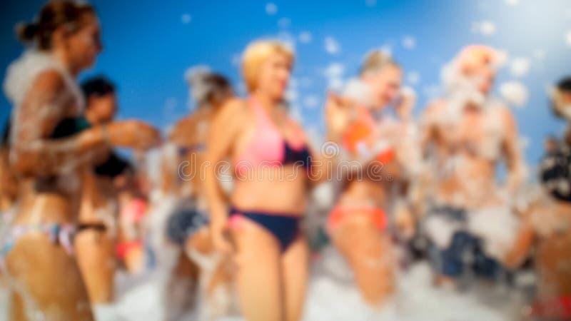 Unscharfes Bild des großen Mengentanzens auf dem Seestrand auf Sommerferienferien Spaß habende und feiernde Leute lizenzfreies stockbild